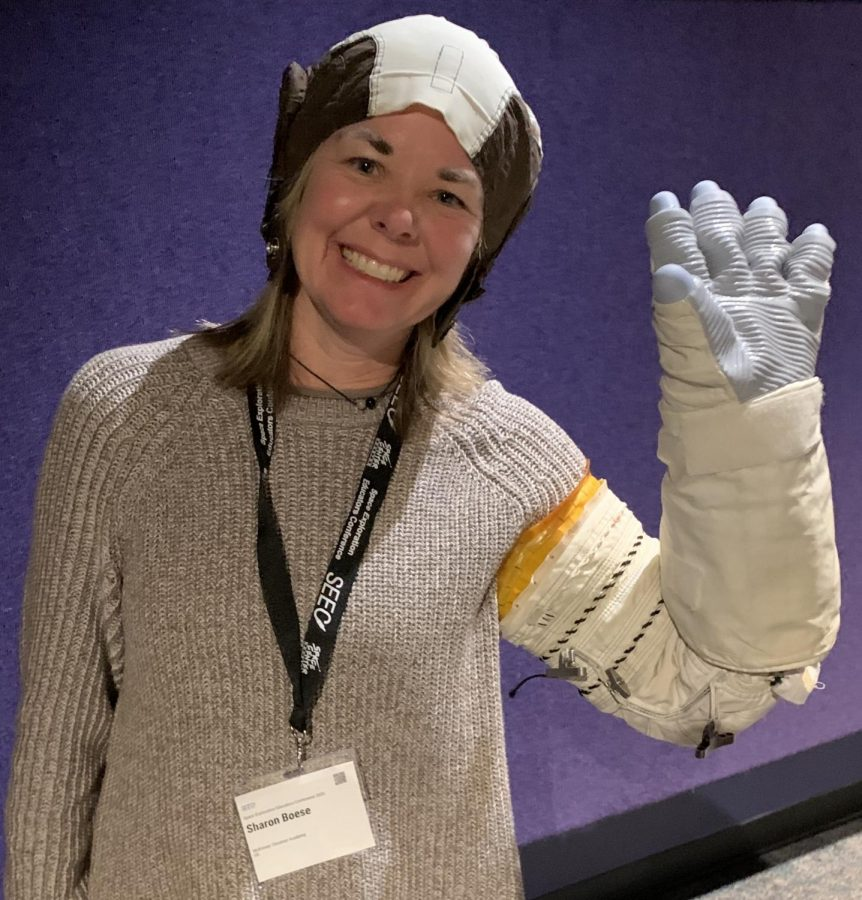 Mrs. Boese poses with an astronauts glove and cap on at the Space Exploration Education Conference.