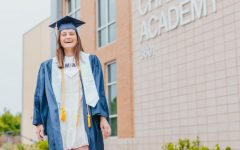 Senior Annie Weichel posing in her cap and gown outside of the McKinney Christian Academy upper school.