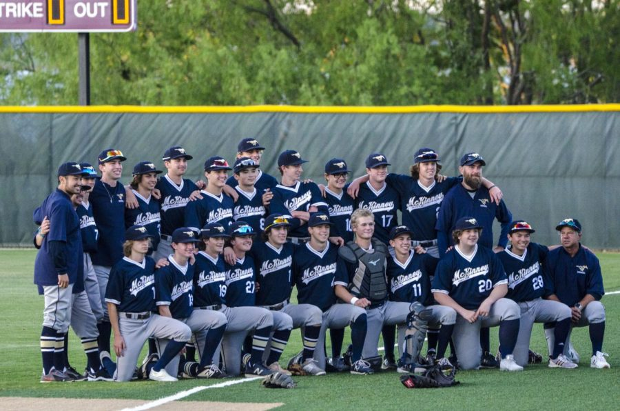 The baseball team takes a group photo after the win.