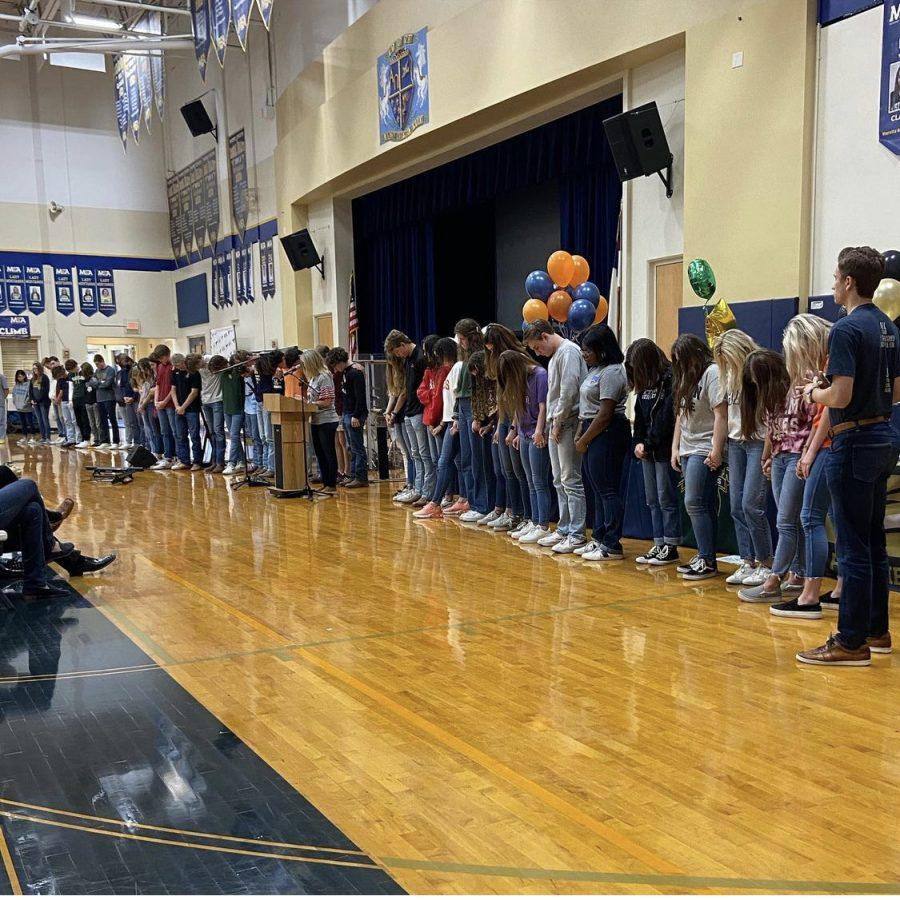 The seniors being prayed over at senior chapel.