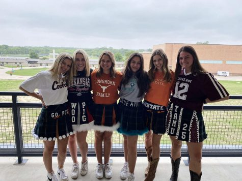 A group of senior girls take a picture wearing their college skirts.