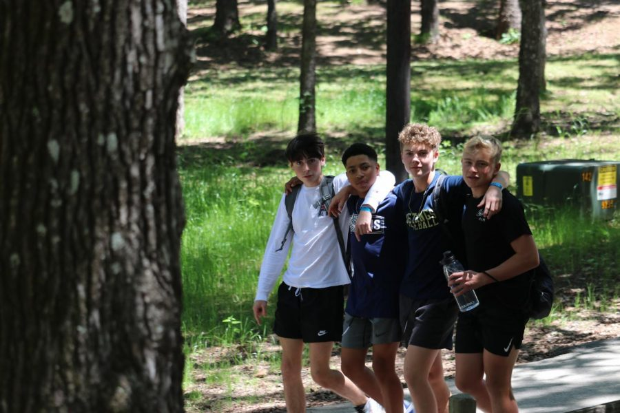 Four eighth grade boys walk through the woods and admire the scenery