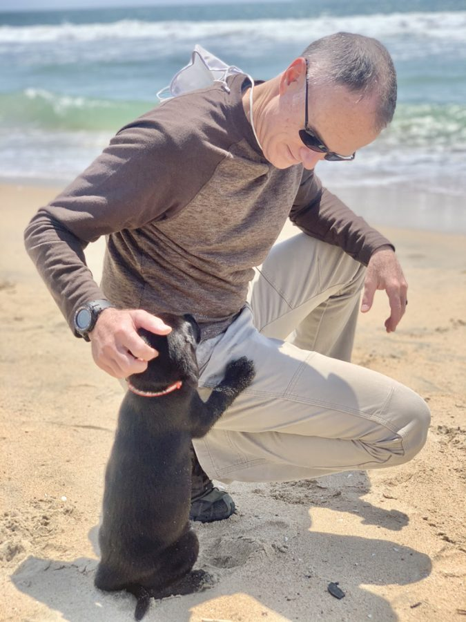 Dr. Mcginn playing with Cowboy at the beach in Long Beach, California.