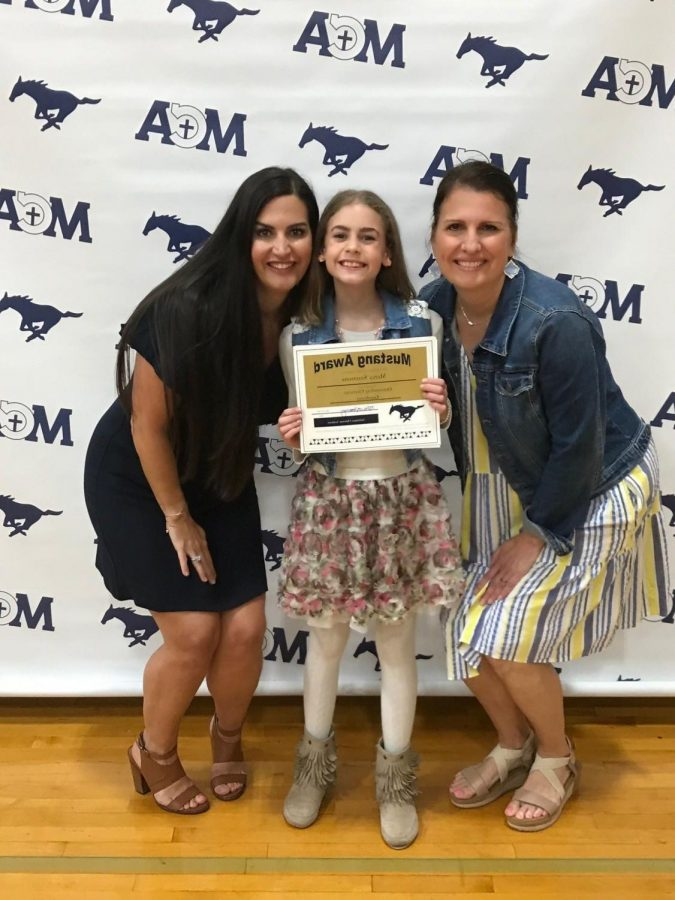 5th grader Mercy Simmons takes a picture with her teachers after getting an award.