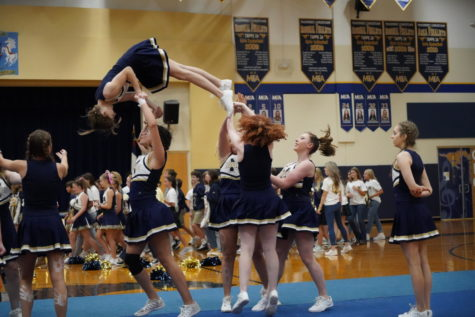 Varsity Cheer performs a stunt during the pep rally on Thursday.