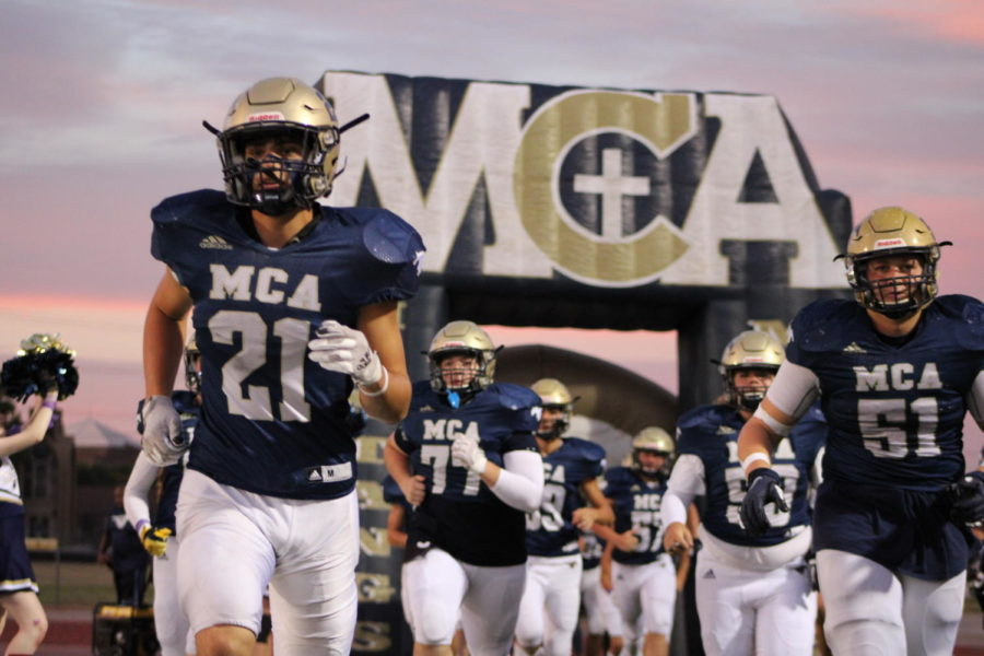 MCA+Varsity+football+team+runs+out+of+their+tunnel+to+get+ready+for+their+game.+