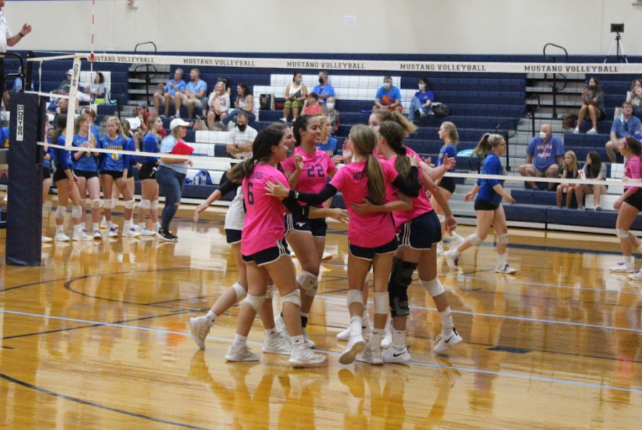 The Lady Mustangs come together to celebrate after winning the point.